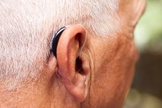 männlicher Hinterkopf mit Hörgerät am Ohr