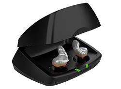Zwei Im-Ohr-Hörgeräte liegen in einer schwarzen Ladestation